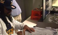 Marshawn Lynch signs a fan's Patriots shirt.