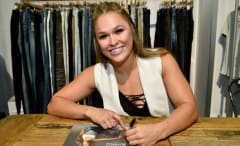 Ronda Rousey signs autographs.