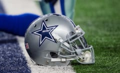 A Dallas Cowboys helmet on the ground.