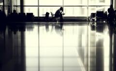 A lone man waits at an airport.