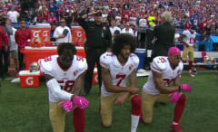 Colin Kaepernick kneels during National Anthem as cop photobombs saluting flag