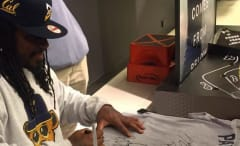 Marshawn Lynch signs a fan's Patriots shirt.