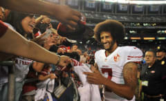Colin Kaepernick signs autographs for fans after a preseason game.