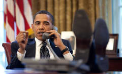 Obama talks on the phone at his desk.