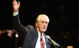 Pat Riley raises his right arm during a ceremony to honor Shaquille O'Neal