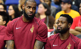 Dwyane Wade and LeBron James sit on the bench.