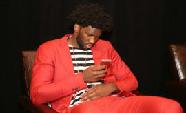 Joel Embiid checks his smartphone at the NBA Draft Lottery.