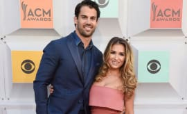 Eric Decker and Jessie James Decker pose on the red carpet of the ACM Awards.