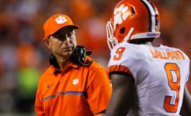Dabo Swinney talks to one of his players during a game