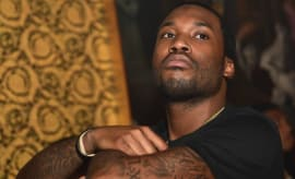 Meek Mill stares at someone.