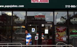 A man walks by a Papa Johns pizza restaurant