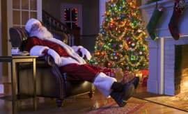 Santa sleeping in chair next to tree