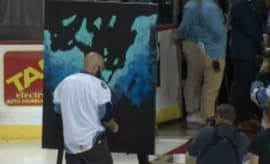 Some guy paints a mural upside down as he sings the National Anthem.