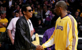Jay-Z and Kobe Bryant shake hands before a Lakers game.