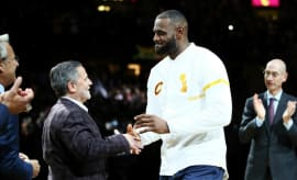 LeBron James and Dan Gilbert shake hands.