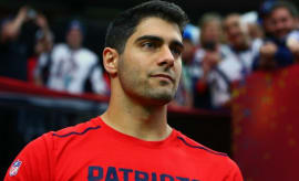 Jimmy Garoppolo stands on the sideline.