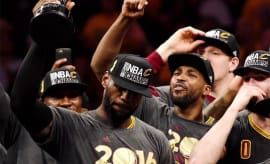 LeBron James holds up the trophy after winning the NBA Championship.