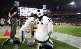 Marshawn Lynch Giorgio Tavecchio of the Oakland Raiders kneel on the sidelines