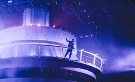 Drake stands atop a giant CN tower replica in front of the OVO Fest crowd.