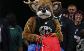 Bucks mascot rides an inflatable Raptor.