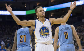 Steph Curry raises his arms during a game.