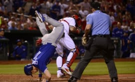 Chris Coghlan jumps over Yadier Molina.