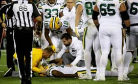 Davante Adams receives medical attention on the field.