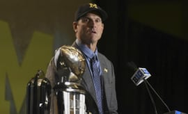 Jim Harbaugh reacts to a reporter's question during a press conference.
