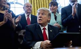 Donald Trump pauses after signing an executive order