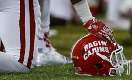 Louisiana-Lafayette player kneels with helmet.
