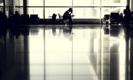 A lone man waits at an airport.