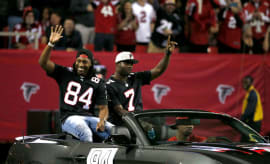 Ex-Falcons Michael Vick and Roddy White wave to the crowd at the Georgia Dome.