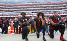 Eli Harold, Colin Kaepernick, and Eric Reid kneel on the sideline