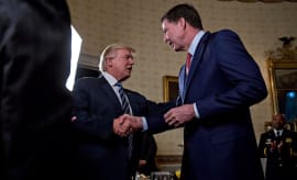 Donald Trump (C) shakes hands with James Comey