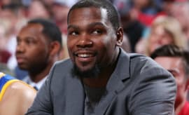 Kevin Durant smiles on the bench.