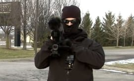A masked man who refuses to give his name films a news taping.