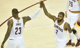 LeBron James high fives Kyrie Irving.