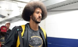 Ex-49ers quarterback Colin Kaepernick arrives with teammates before the game against the Chargers