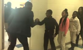 A Charlotte, NC teacher dishes out personalized handshakes to each student.