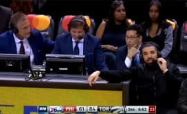 Drake speaks with Raptors announcers during their win over the 76ers.