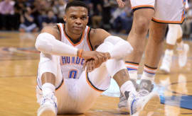 Russell Westbrook sits on the floor during a Thunder game.