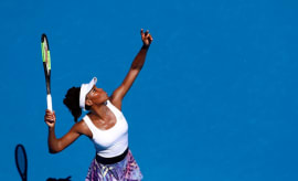 Venus Williams tosses up a serve.