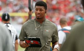 Jameis Winston stands on the sideline.