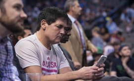 Mark Cuban checks his phone during a Mavericks game.