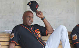 Barry Bonds sits in dugout during Giants' Spring Training game.