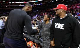 LeBron James shakes Kendrick Lamar's hand during a game in Los Angeles.