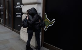 A couple wearing black hoodies with faces hidden, hug on Regent Street