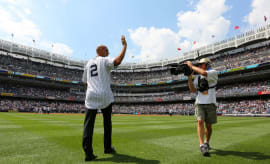 Derek Jeter waves to the crowd as the Yankees introduce the 1996 World Series team.