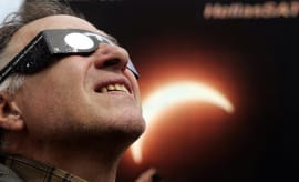 A man watches a solar eclipse.