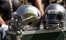 Two Baylor football helmets sitting on the sidelines.